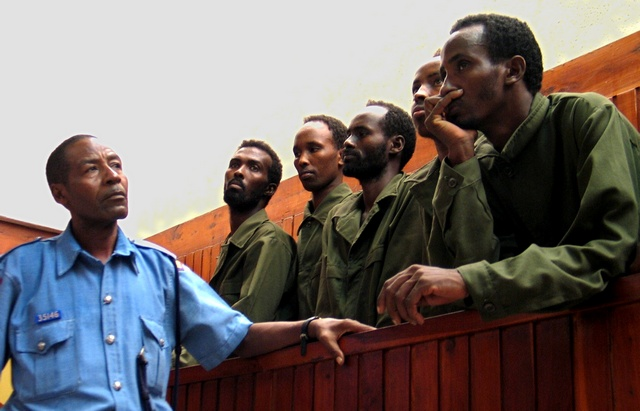 A Kenyan policeman stands guard next to Somali nationals at the law courts in the Kenya's costal City of Mombassa